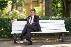 A tired man in a business suit left the office and went in the Park. he is sitting on a white bench alone and wait someone. He is alone royalty free stock photo