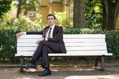 A tired man in a business suit left the office and went in the Park. he is sitting on a white bench alone and wait someone. He is alone royalty free stock image
