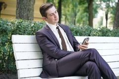 A young man in a business suit left the office and came to the Park. he sits on a white bench alone and talks on the phone. A tired man in a business suit left stock photo