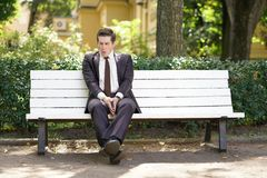 A tired man in a business suit left the office in the Park, sitting on a white bench alone and yawns. A tired man in a business suit left the office and went in stock images