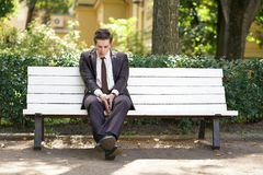 A tired man in a business suit left the office in the Park, sitting on a white bench alone and yawns. A tired man in a business suit left the office and went in royalty free stock photo