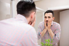 Tired man checking his face in mirror Stock Photo