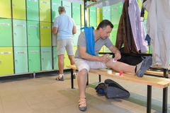 Tired man cleaning wound in locker room. Tired men cleaning a wound in locker room Royalty Free Stock Photo