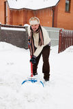 Tired man cleans snow. Tired mature man cleans snow near the house stock photo