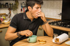 Tired Man with Coffee Sitting at Kitchen Table Royalty Free Stock Images