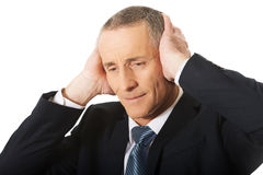 Tired man covering ears with hands Stock Photos