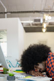 Tired man with curly hair sleeping at desk in office Royalty Free Stock Image