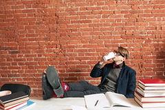 Tired man drinking coffee to continue study. Exhausted student need more energy to learn material, free space on brick wall background. Charging, education Stock Photos