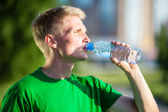 Tired man drinking water from a plastic bottle Royalty Free Stock Images