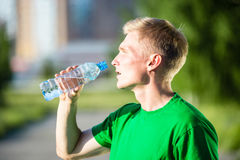 Tired man drinking water from a plastic bottle Stock Photo