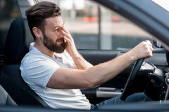 Tired man driving a car Royalty Free Stock Images