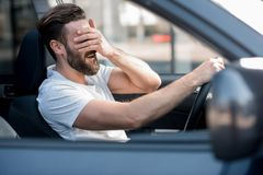 Tired man driving a car. Tired man dressed casual in white t-shirt driving a car with headache in the city Stock Images