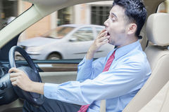 Tired man driving a car. Portrait of businessman driving a car while yawning, shot on the road Royalty Free Stock Photos