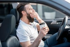 Tired man driving a car. Tired man yawning on the front seat of the car holding coffee to go stock images