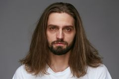 Tired Man With Exhausted Face And Dark Circles Under Eyes. And Long Hair On Gray Background. High Resolution stock image