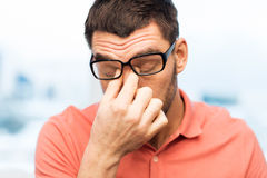 Tired man in eyeglasses rubbing eyes at home. People, eyesight, stress, overwork and business concept - tired man in eyeglasses rubbing his eyes at home or work Royalty Free Stock Images