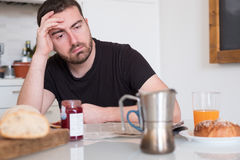 Tired man feeling bad during the morning breakfast Royalty Free Stock Images