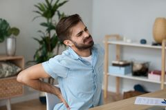 Tired man feeling pain in back suffering from lower backache royalty free stock image