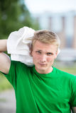 Tired man after fitness time and exercising. With white towel Royalty Free Stock Images
