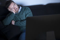 Tired man in front of television Royalty Free Stock Photography