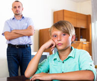 Tired man and frustrated teenager. Unhappy men and frustrated teenager having quarrel at home Stock Images