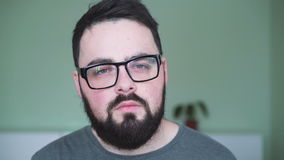Tired man in glasses looking to camera in 4K stock video footage