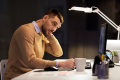 Tired man having neck ache working at night office. Business, deadline and health concept - tired man working at night office and having neck ache royalty free stock photography