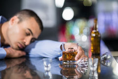 Tired man having a whiskey and sleeping on a counter Stock Photo