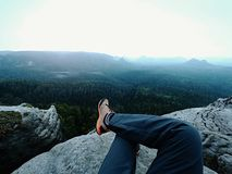 Tired man hiker lay down and enjoy view into landscape over his tired legs in tourist boots Stock Image