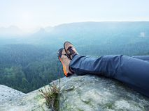 Tired man hiker lay down and enjoy view into landscape over his tired legs in tourist boots Royalty Free Stock Images