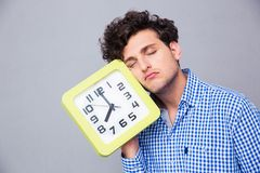 Tired man holding big clock Royalty Free Stock Photography