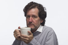 Tired man holding coffee mug, horizontal Stock Images