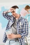 Tired man holding paint can and brush with woman painting in background Royalty Free Stock Photo