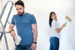 Tired man during home renovation arguing with girlfriend. Stressed couple arguing during home renovation stock photo