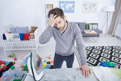 Tired man ironing baby clothes Royalty Free Stock Photos