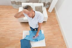 Tired Man Ironing Clothes Stock Photography