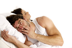 Tired man laid in white bed next to a sleeping woman Stock Images