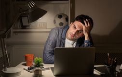 Exhausted man working late at home on laptop royalty free stock photography