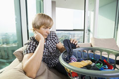 Tired man with laundry basket sitting on sofa at home Royalty Free Stock Photo