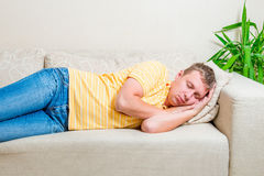 Tired man lay down to take a nap on the sofa. In the living room stock photo