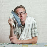 Tired man lean his cheek to iron and close eyes with happy smile. Man householder concept Stock Images