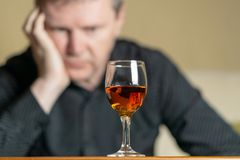 Tired man leaning his head on a glass of brandy. Man out of focus stock photo
