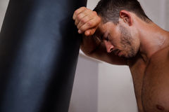 Tired man leaning on punching bag Stock Photo