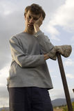 Tired man leaning on spade Stock Photo