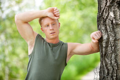Tired man leaning on tree Stock Image