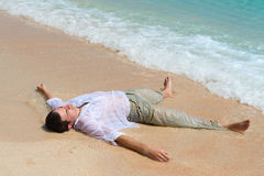 Tired man lie on sandy beach Royalty Free Stock Images