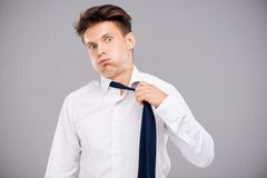 Tired man loosening his tie. Overworked tired young man loosening his tie stock photos