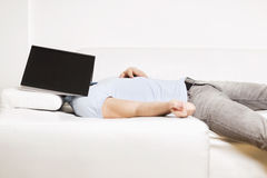 Tired man lying on couch with book on his face. Royalty Free Stock Photography