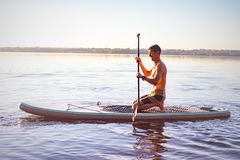 Tired man paddling on a SUP board on large river. Stand up paddle boarding - awesome active outdoor training royalty free stock photo