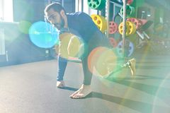 Tired man with prosthetic leg resting after exercise. Tired handsome young bearded man with prosthetic leg standing on one knee and leaning on hand while resting royalty free stock photos